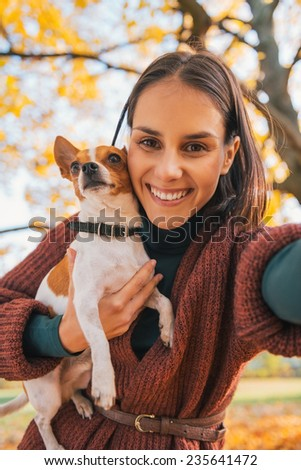 Portrait of smiling young woman with dog outdoors in autumn making selfie - stock photo