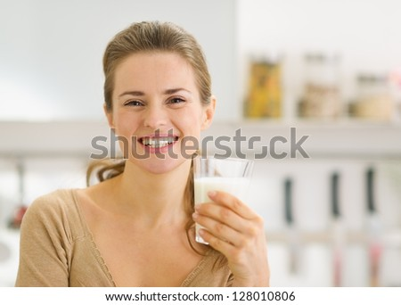 Portrait of smiling young woman with glass of milk in kitchen - stock photo