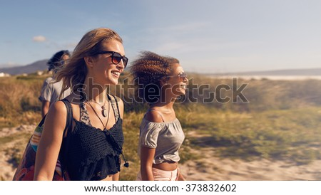Portrait of smiling young women going on the beach. Female friends on sea shore on summer day, beach vacation. - stock photo