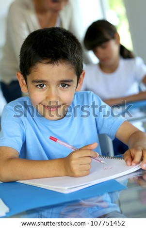Portrait of smilng young boy sitting in classroom - stock photo