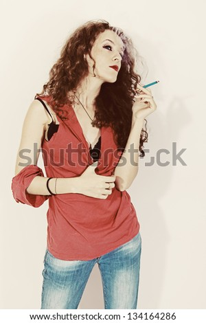 Portrait of smoking young brunette woman with long curly hair on a white background. Retro style