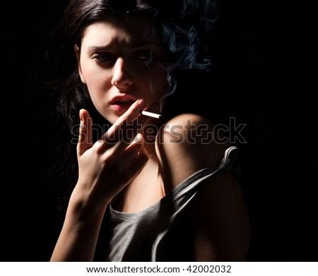 portrait of smoking young woman with cigarette on black - stock photo