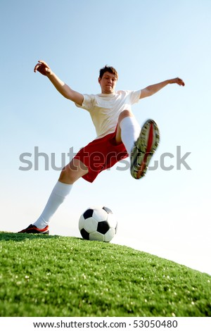 Portrait of soccer player before kicking ball on football field - stock photo
