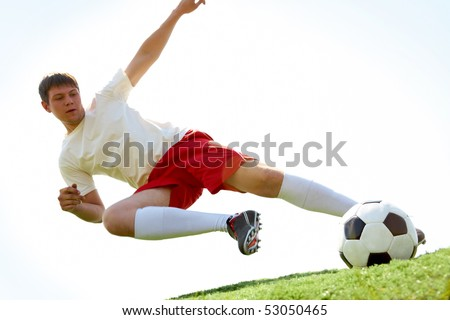 Portrait of soccer player making flying kick at ball during game - stock photo
