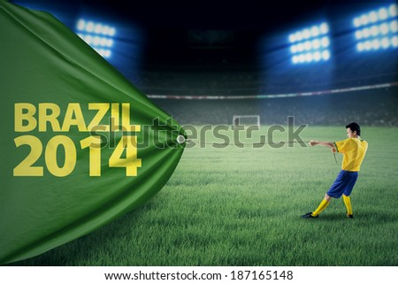 Portrait of soccer player pulling a banner of football competition. Isolated on white