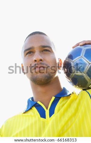 Portrait of soccer player with ball on shoulder - stock photo