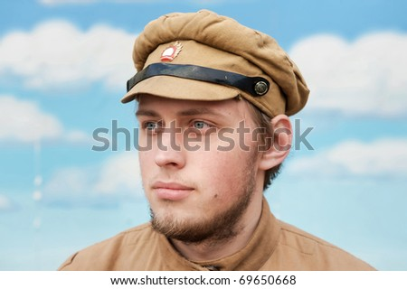 Portrait of soldier in uniform of World War 1 on the background of blue sky. Costume accord the times of World War I. Photo made at cinema city Cinevilla in Latvia. - stock photo