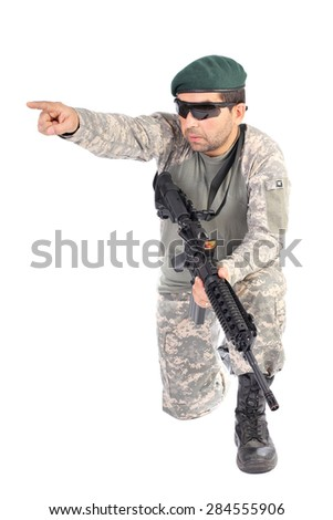 Portrait of soldier or commander holding his rifle and pointing  with finger over white background - stock photo