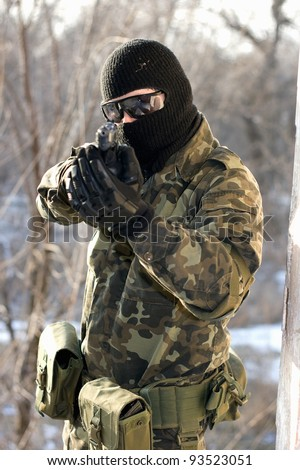 Portrait of soldier with a handgun in his hands - stock photo