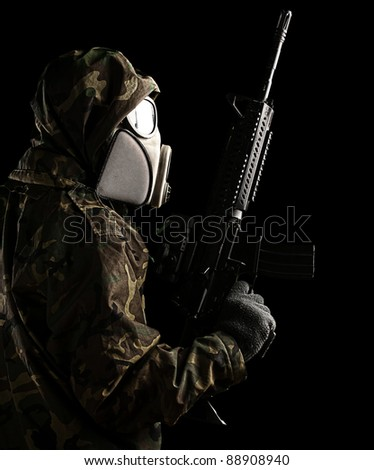 portrait of soldier with mask and rifle against a black background
