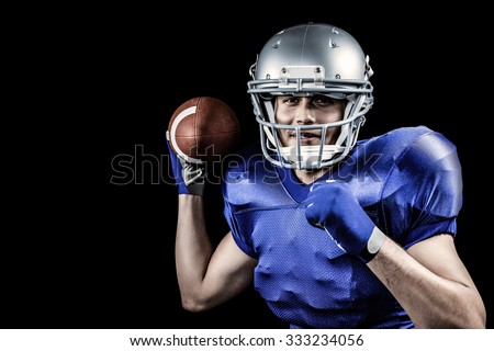 Portrait of sportsman smiling while throwing ball against black