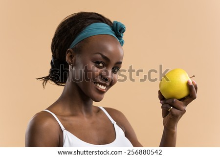 Portrait of sporty african smiling woman eating green apple on beige studio background, looking at camera - stock photo
