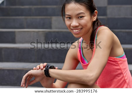portrait of sporty asian chinese woman sitting outdoors checking workout time on wearable technology watch after run