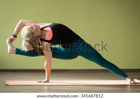 Portrait of sporty beautiful blond woman in sportswear working out indoors, doing Vishvamitrasana Side bend Posture on orange eco mat, strengthening upper body, wrists, legs, stretching hips - stock photo