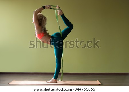 Portrait of sporty beautiful blond young woman in sportswear working out indoors, doing balance back bend, Natarajasana, Lord of the Dance posture, variation with belt on orange mat, full length - stock photo