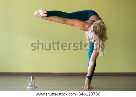 Portrait of sporty beautiful blond young woman in sportswear working out indoors, doing exercises for groins, hips, thighs and calf muscles flexibility - stock photo