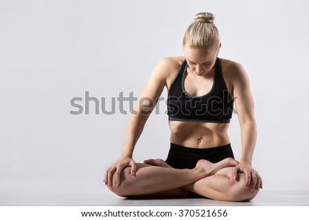Portrait of sporty beautiful young woman practicing yoga, sitting with crossed legs, in Padmasana, Lotus Posture, performing Upward Abdominal Lock, Uddiyana Bandha, copy space, studio - stock photo