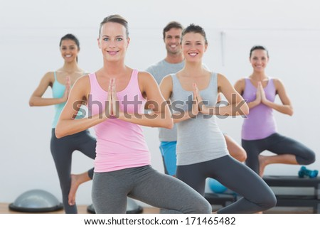 Portrait of sporty class with joined hands standing in fitness studio - stock photo