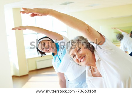 Portrait of sporty females doing physical exercise in sport gym - stock photo