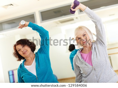 Portrait of sporty females doing physical exercise with barbells in sport gym - stock photo