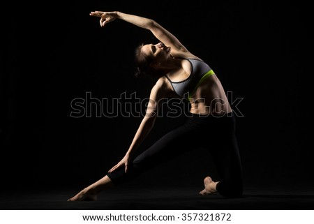 Portrait of sporty fit happy beautiful young woman in sportswear bra and black pants working out, doing side bend Parighasana posture, Gate Pose, studio full length, black background - stock photo