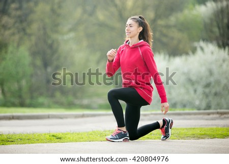 Portrait of sporty happy woman doing stretching exercises in park before training. Female athlete preparing for jogging outdoors. Runner doing lunge exercises. Sport active lifestyle concept - stock photo