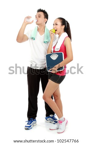 Portrait of sporty healthy young woman with weight scale and man drinking water isolated on white background - stock photo