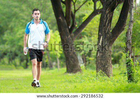 portrait of sporty male runner walking by at roadsidewhile take a breath after tired running with copy space - stock photo