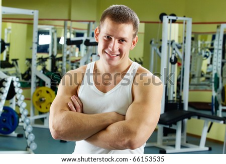 Portrait of sporty man with crossed arms looking at camera - stock photo