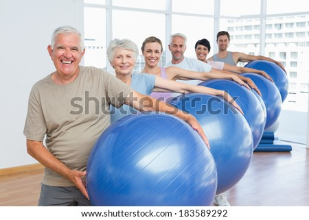 Portrait of sporty people carrying exercise balls in a row at bright gym - stock photo