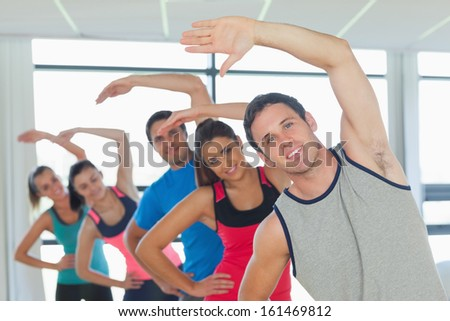Portrait of sporty people doing power fitness exercise in row at yoga class