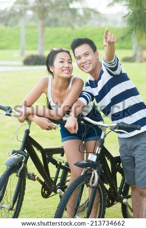 Portrait of sporty Vietnamese couple with bikes where man pointing at something - stock photo