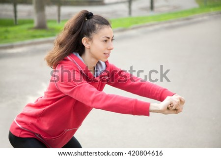 Portrait of sporty woman doing stretching exercises in park before training. Female athlete preparing for jogging outdoors. Runner doing side lunges. Sport active lifestyle concept. Close-up - stock photo