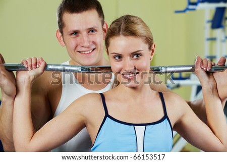 Portrait of sporty woman holding dumbbell and her trainer supporting - stock photo