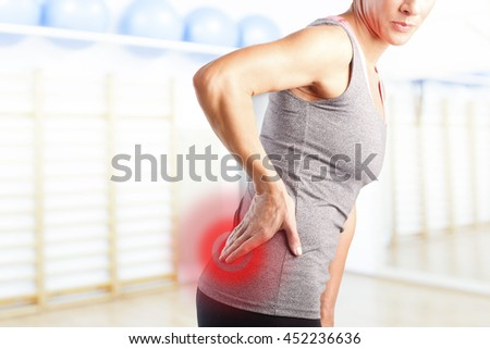 Portrait of sporty woman putting her hand on red spot on while has sport injury in her waist.  - stock photo