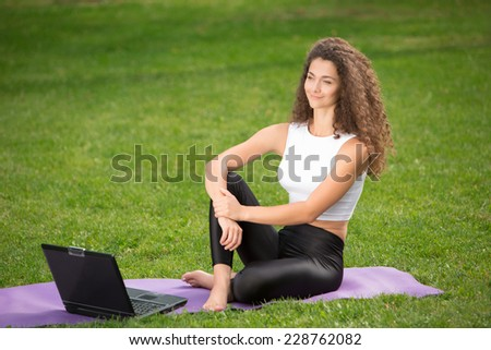Portrait of sporty young businesswoman sitting with laptop. Green grass background - stock photo