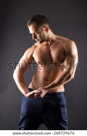 Portrait of sporty young muscular male topless shirtless athletic macho standing posing over black background. Torso of strong man in jeans against dark background.