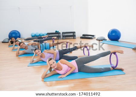 Portrait of sporty young people with exercising rings in fitness studio