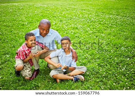 Portrait of squatted african father with two little sons on green lawn