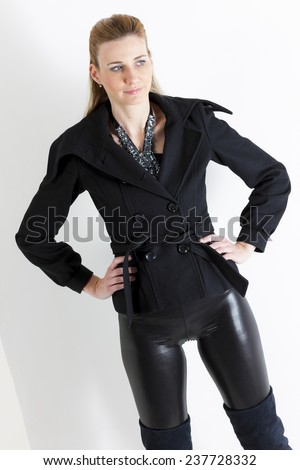 portrait of standing woman wearing black clothes and black boots - stock photo