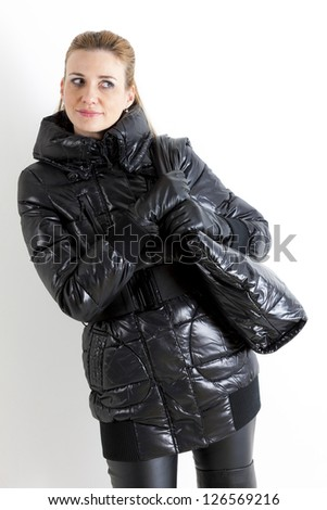 portrait of standing woman wearing black clothes with a handbag - stock photo