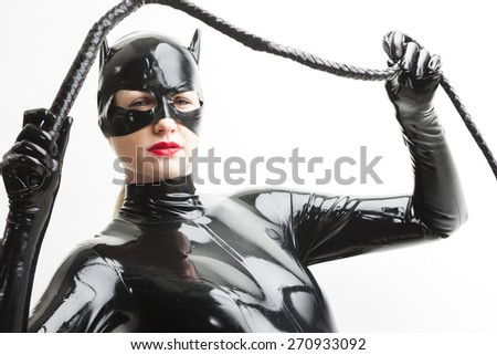 portrait of standing woman wearing latex clothes with a whip