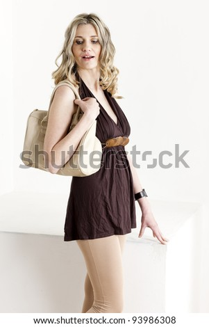 portrait of standing woman wearing summer clothes with a handbag - stock photo