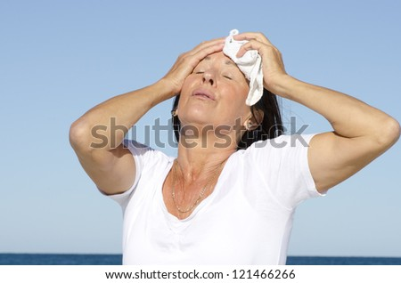 Portrait of stressed and exhausted looking middle aged woman trying to cool down face, isolated outdoor with blue sky as background and copy space. - stock photo