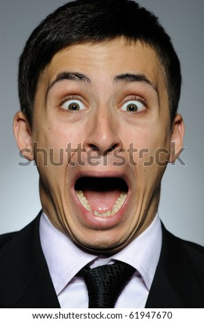 Portrait of stressed  business man in formal suit and black tie screaming.  gray background - stock photo