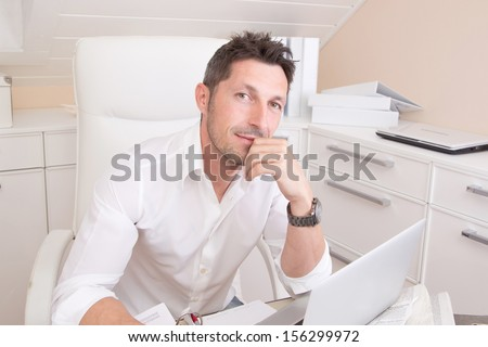 Portrait of stressed man sitting at desk. - stock photo