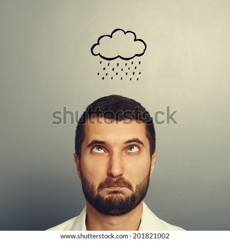 portrait of stressed man with drawing storm cloud over grey background - stock photo