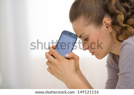 Portrait of stressed young woman with cell phone - stock photo