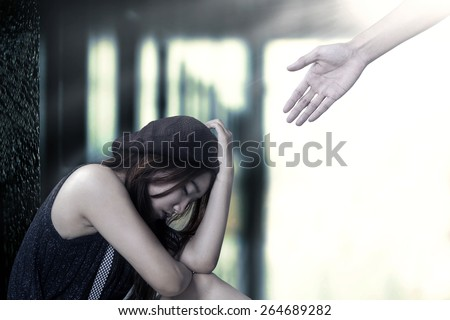 Portrait of stressful teenage girl sitting on the floor with a hand coming out from bright background offers help - stock photo