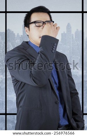 Portrait of stressful young businessman standing near the window while massage his head - stock photo